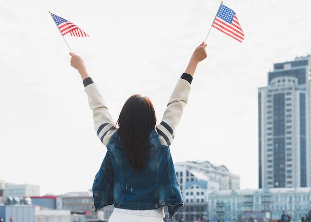 Frau, die amerikanische flaggen in den händen wellenartig bewegt