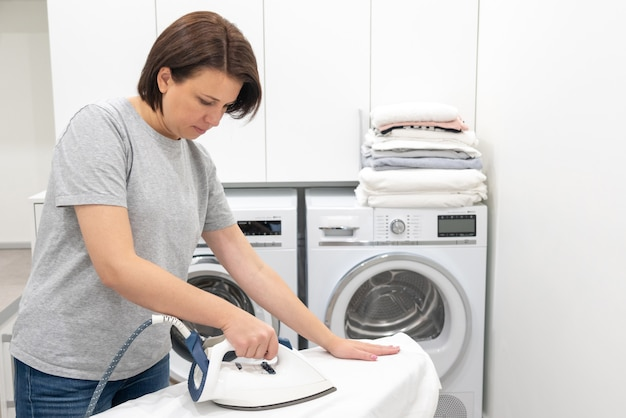 Frau, die an bord in der waschküche mit waschmaschine bügelt