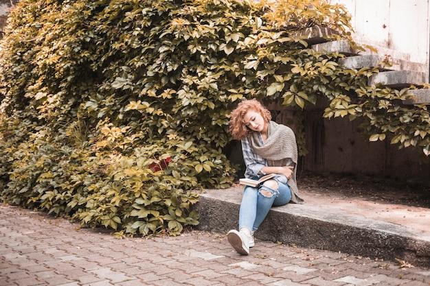 Frau, die an bord sitzt und buch nahe pflanze liest