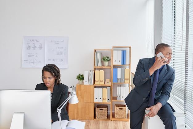 Frau, die an computer und geschäftsmann sprechen am telefon im büro arbeitet