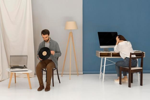 Frau, die an computer und mann arbeitet, die musik hören
