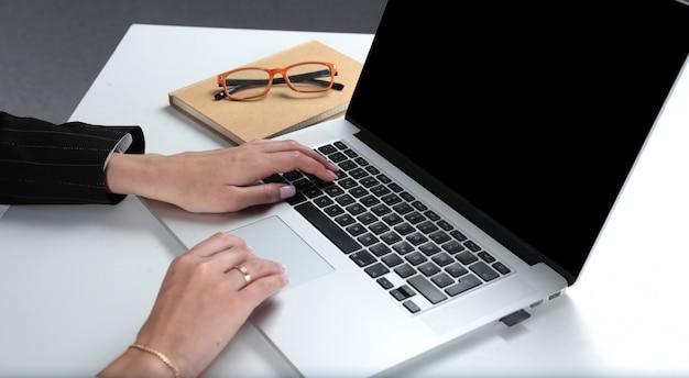 Frau, die an dem laptop, sitzend am schreibtisch arbeitet.