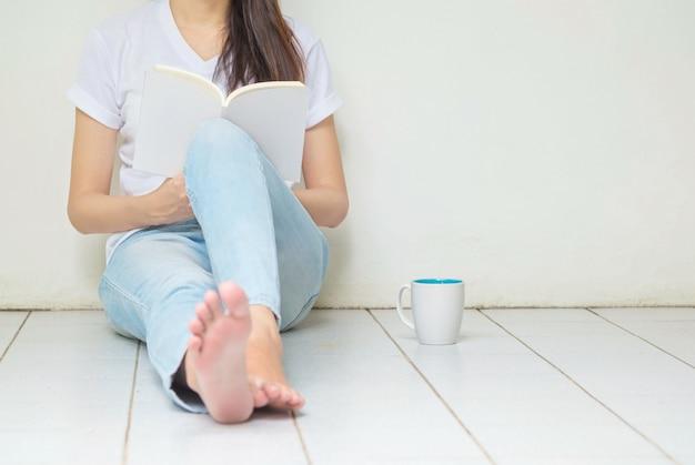 Frau, die an der ecke des hauses für das lesen eines buches in der freizeit am nachmittag sitzt