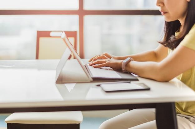 Frau, die an der hand im büro arbeitet und am tastaturcomputer tippt