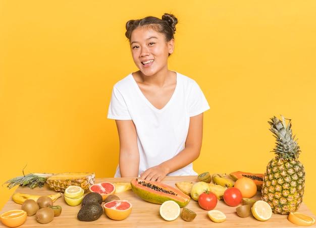 Frau, die an der kamera hinter einem tisch mit früchten lächelt