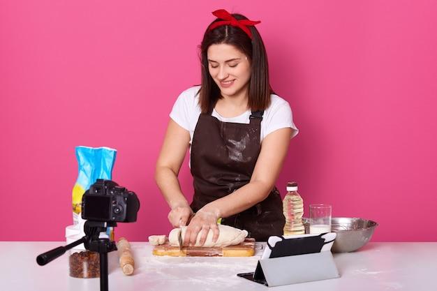 Frau, die an der küche kocht, rohen kuchen mit messer schneidet, vergnügen während des prozesses erhält, schüssel, öl, brett habend