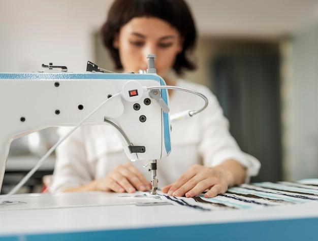 Frau, die an der nähmaschine arbeitet