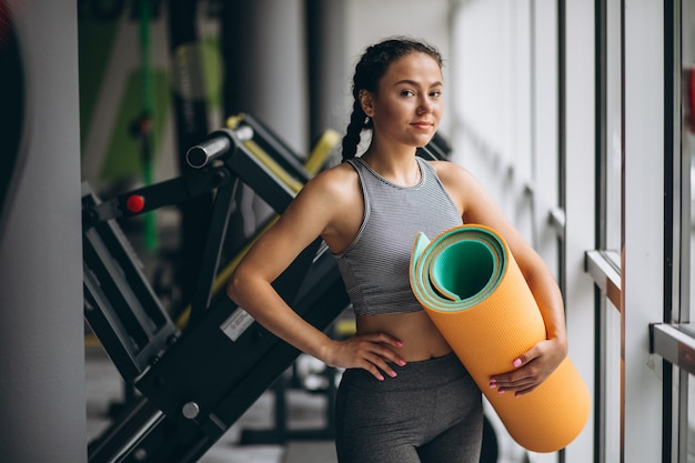 Frau, die an der turnhalle hält yogamatte ausübt