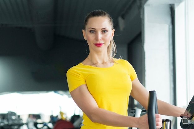 Frau, die an der turnhalle in einem ausdauertraining des elliptischen trainers trainiert