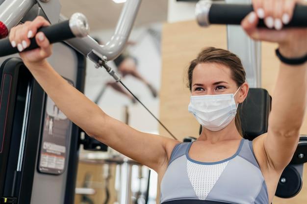 Frau, die an der turnhalle während der pandemie ausarbeitet