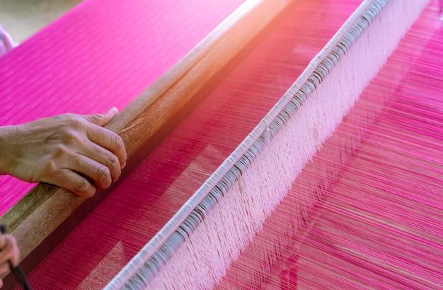 Frau, die an der webmaschine für handgemachten stoff arbeitet. textilweberei. weben mit traditionellen handwebstühlen auf den langen baumwollsträngen.