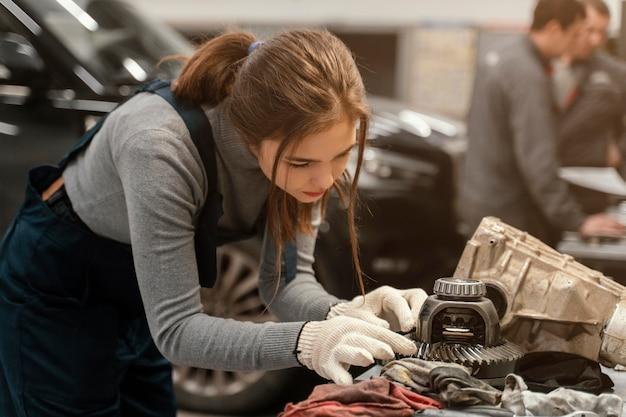 Frau, die an einem autoservice arbeitet