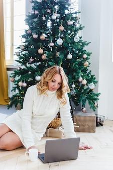 Frau, die an einem computer arbeitet oder studiert, innenraum wird für weihnachten verziert