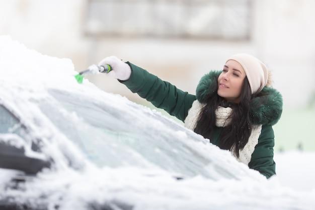 Frau, die an einem eiskalten wintertag versucht, schnee vom autodach zu bürsten.