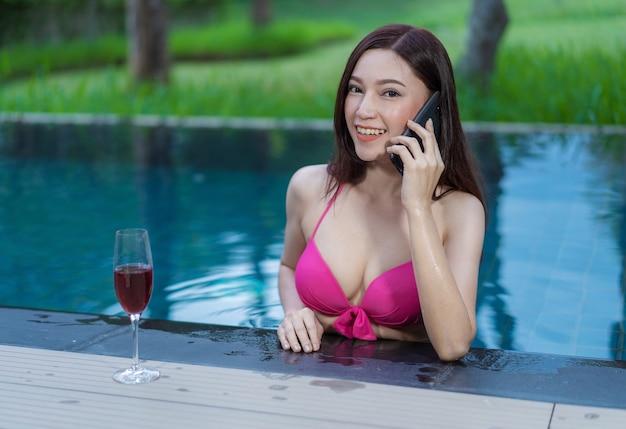 Frau, die an einem handy im swimmingpool spricht