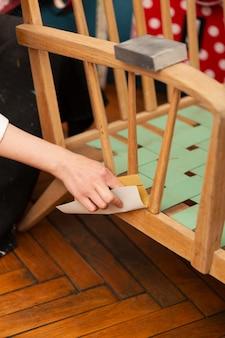 Frau, die an einem hölzernen möbelstück arbeitet