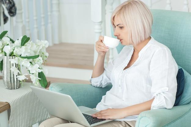 Frau, die an einem laptop arbeitet und kaffee trinkt