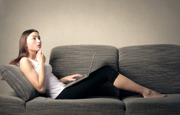 Frau, die an einem laptop auf einem sofa arbeitet