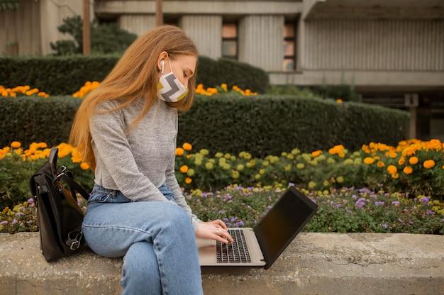 Frau, die an einem laptop im freien arbeitet, während sie eine medizinische maske trägt