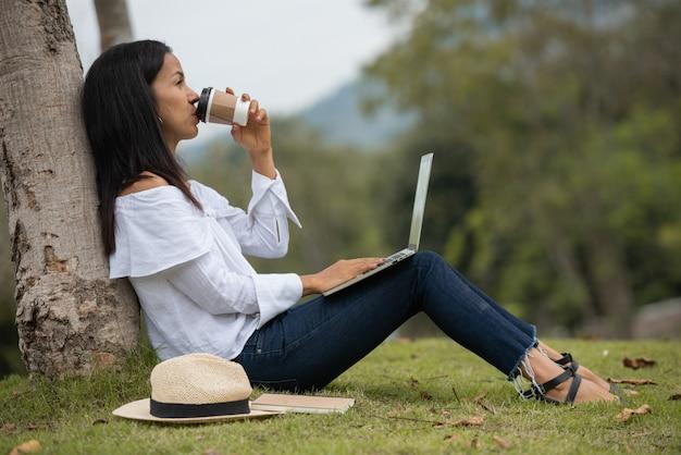 Frau, die an einem laptop in der natur arbeitet
