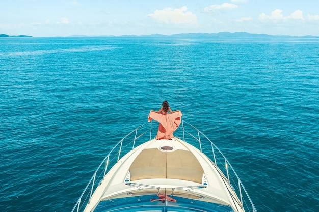Frau, die an einem sonnigen sommertag auf dem bug einer yacht steht, brise der haarentwicklung, schönes meer an der oberfläche
