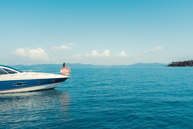 Frau, die an einem sonnigen sommertag auf der nase der yacht steht, brise haare entwickeln, schönes meer an der oberfläche