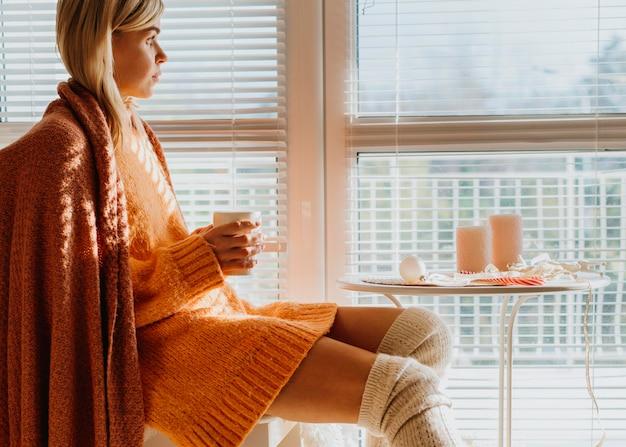 Frau, die an einem tisch mit einer tasse tee sitzt