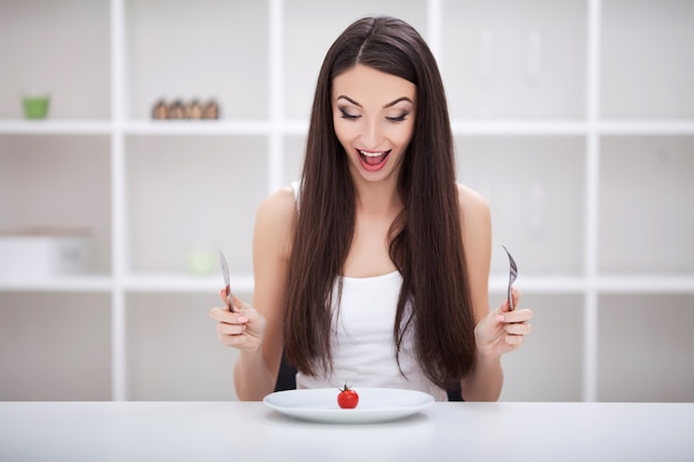 Frau, die an einem tisch mit gemüse auf einer platte sitzt