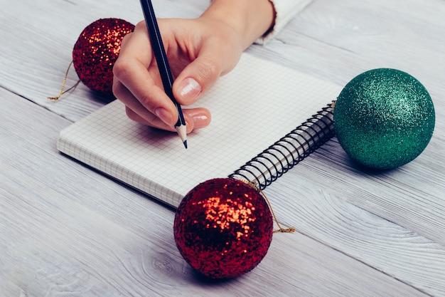 Frau, die an einem tisch mit weihnachtsbällen sitzt und in ein notizbuch mit einem bleistift schreibt