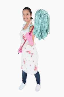 Frau, die an einen mopp mit handschuhen hält