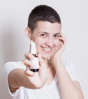 Frau, die an hand kamera mit hautprodukt betrachtet
