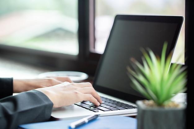 Frau, die an ihrem laptop auf einer terrasse arbeitet