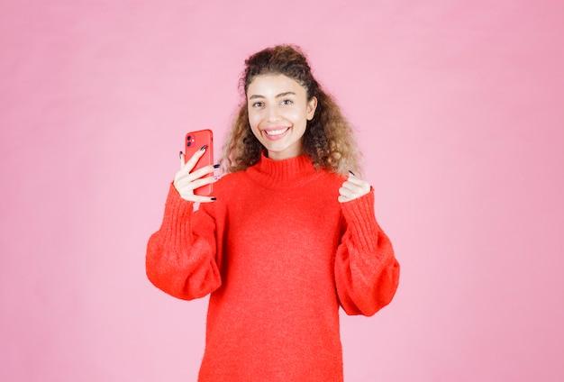 Frau, die an ihrem neuen smartphone sms schreibt und sich glücklich fühlt.