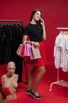 Frau, die an ihrem telefon am einkaufen spricht