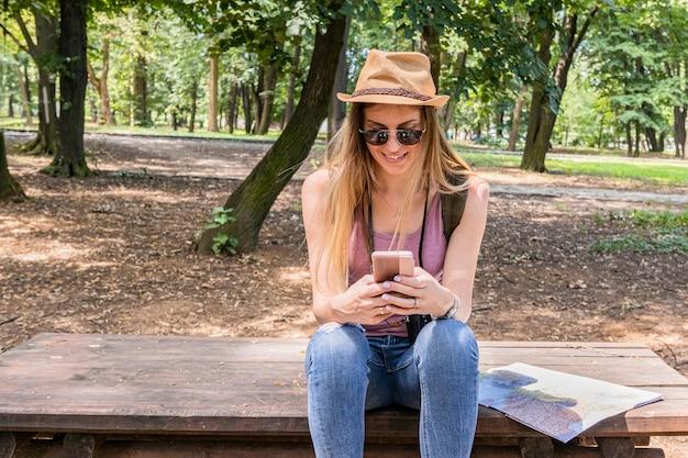 Frau, die an ihrem telefon nahe bei einer karte lächelt