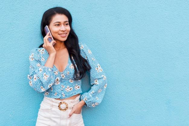Frau, die an ihrem telefon spricht und weg schaut