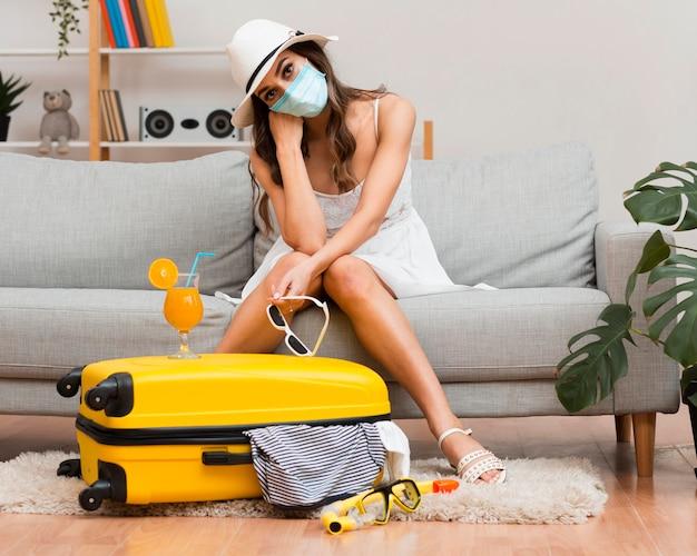 Frau, die an ihren verschobenen urlaub denkt, während sie eine medizinische maske trägt