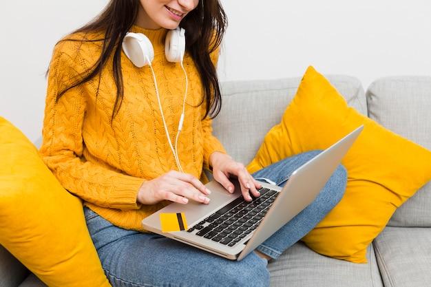 Frau, die an laptop beim tragen von kopfhörern arbeitet