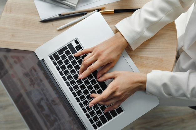 Frau, die an laptop-computerhänden nah arbeitet. hand auf tastatur nahaufnahme nahaufnahme einer weiblichen hand beschäftigt, die auf einem laptop tippt. zuhause arbeiten. konzept der quarantäne und sozialen distanzierung.