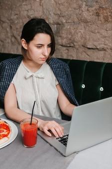 Frau, die an laptop im café arbeitet