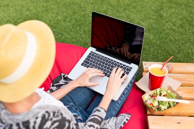 Frau, die an laptop von hinten arbeitet