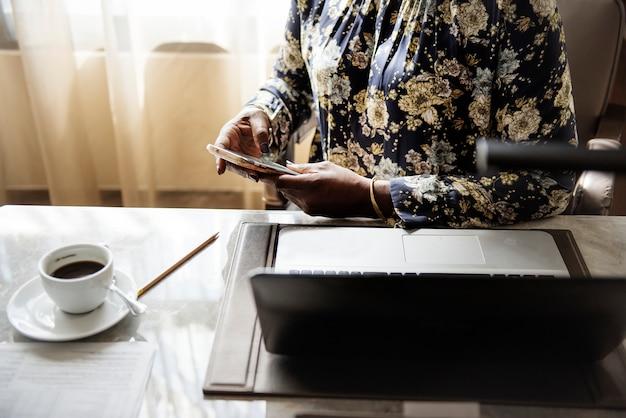 Frau, die an mobile im hotelzimmer arbeitet