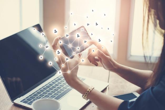 Frau, die an notizbuchcomputer mit sozialen internetikonen arbeitet. moderner lebensstil mit mobiler online-technologie.