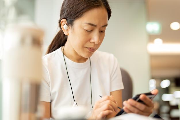 Frau, die an smartphone mit drahtlosen kopfhörern im café arbeitet.