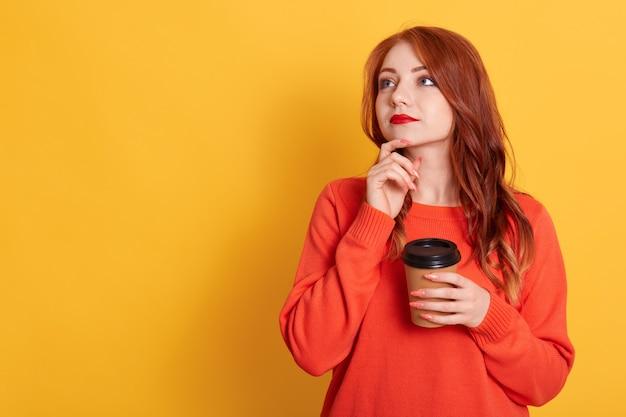 Frau, die an zukunft denkt, wegwerfbare tasse kaffee hält und beiseite schaut