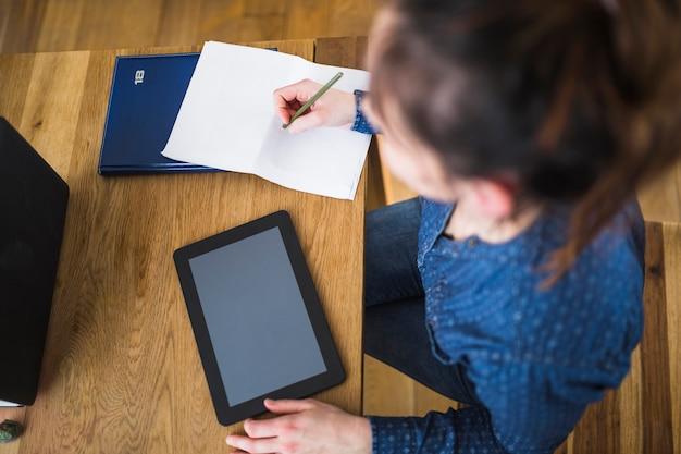 Frau, die anmerkungen auf papier mit digitaler tablette über hölzernem schreibtisch schreibt