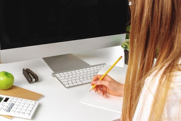 Frau, die anmerkungen im notizblock in einem büro bildet