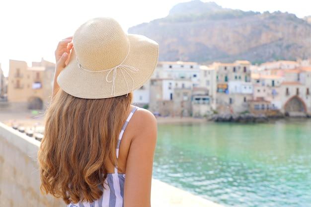 Frau, die ansicht der alten stadt cefalu in sizilien, italien genießt
