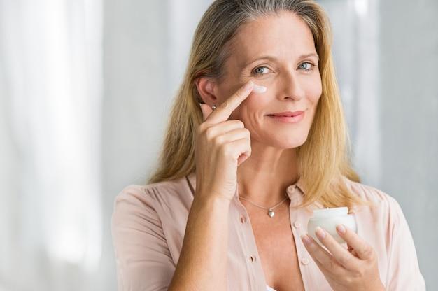 Frau, die anti-aging-lotion auf gesicht aufträgt