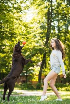 Frau, die anziehenden ball des hundes im mund betrachtet